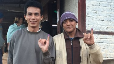 Men from different generations display their inked fingers after voting.