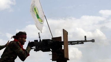 A Shiite militiaman fires a weapon during clashes with IS in Iraq.