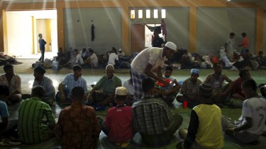 Rohingya and Bangladeshi migrants receive food inside a temporary shelter in Lhoksukon in Aceh.