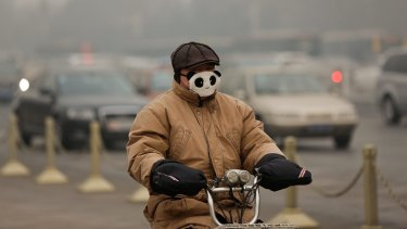 A man rides a bicycle on a 'bad air' day in Beijing last year.