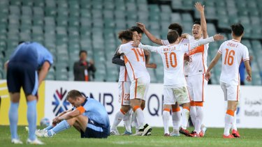 Down and out: Shandong Luneng players celebrate as Sydney FC players slump to the ground at the final whistle.