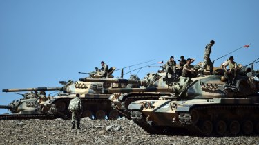 Turkish tanks line up on a hill overlooking the Syrian city of Kobane, near the Turkish border.