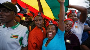 Protesters raise their fists under a large national flag, at a demonstration of tens of thousands at Zimbabwe Grounds in Harare.