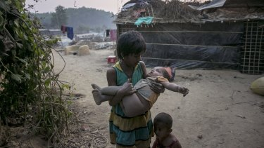 A girl carries a toddler in Bangladesh. A one-metre rise in sea level would submerge one-fifth of the country, displacing 30 million people.