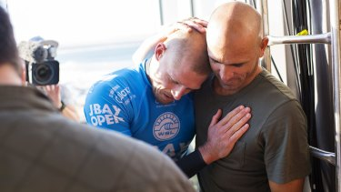 Glad you're all right: Kelly Slater embraces fellow world champion Mick Fanning after the Australian surfer's shark attack.