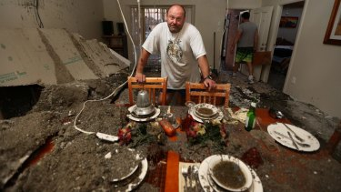 Just yesterday this house sold at auction for a record price. Frank Partic stands at a set dinning table amongst ruins.