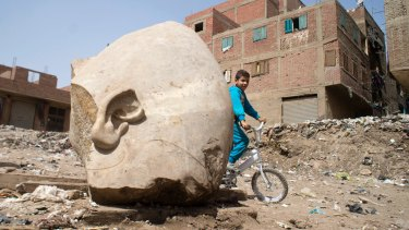 A boy rides his bicycle past the recently discovered statue in a Cairo slum.