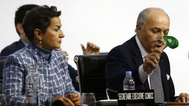 Christiana Figueres (left) watches on as French Foreign Minister and president of the COP21 Laurent Fabius uses to hammer to mark the adoption of the Paris climate agreement in December 2015.