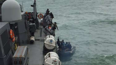 An Indonesian Navy seaboat picks up AirAsia debris retrieved by the Republic of Singapore Navy vessel RSS Valour.