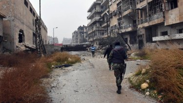 Syrian troops and pro-government gunmen marching through the streets of east Aleppo on Tuesday.