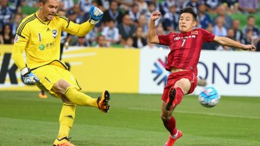 Victory goalkeeper Danny Vukovic is challenged by Wu Lei of Shanghai SIPG.