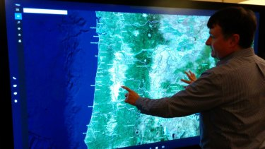 Microsoft's Brian Eskridge uses the Surface Hub to demonstrate the location of a Portland, Oregon, manufacturing plant.