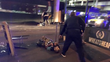 One of the suspects, wearing what appear to be canisters strapped to his chest, lying on the ground after being shot by police outside Borough Market in London.