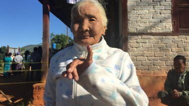 An elderly woman shows her inked finger.