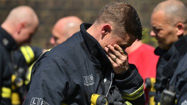 A firefighter breaks down before a minute's silence near Grenfell Tower on June 19, 2017..