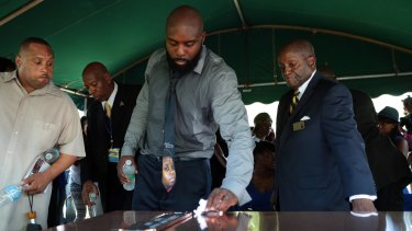 Michael Brown snr wipes the top of the vault containing the casket of his son at his funeral in August.