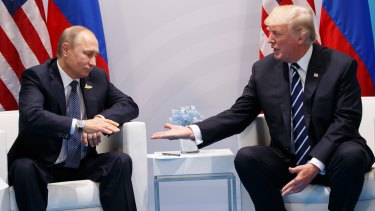 President Donald Trump reaches to shakes hands with Russian President Vladimir Putin at the G20 summit.