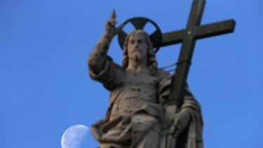 The moon sets behind the statue of Jesus.