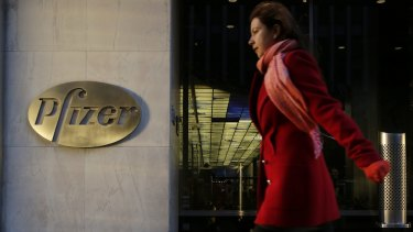 A woman passes Pfizer's current world headquarters in New York. Pfizer and Allergan will join in a $US160 billion deal to create the world's largest drugmaker.
