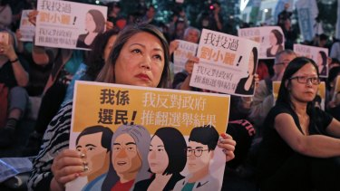 "Protesters hold posters featuring the newly elected HK pro-democracy lawmakers of the legislature council, ""Long Hair"" Leung Kwok-hung, Nathan Law Kwun-chung, Lau Siu-lai and Edward Yiu Chung-yim during a demonstration in Hong Kong on Saturday."