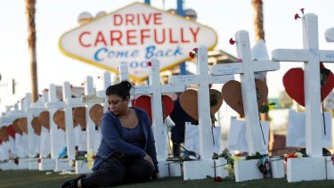 Cece Navarrette sits near a cross for her cousin, Bailey Schweitzer, who was among 58 people killed.