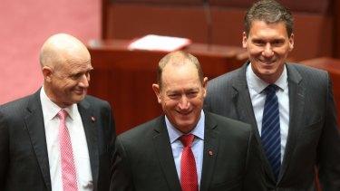 New senator Fraser Anning is escorted by fellow crossbench senators David Leyonhjelm and Cory Bernardi on Monday.
