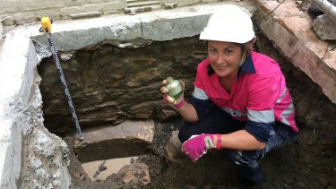 Archaeologist Tina King with a WWII-era bottle found in the test pit at the Harris Terrace.