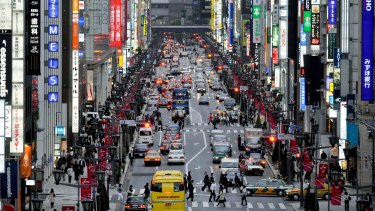 Pedestrians and cars move along the main street of the Ginza district of Tokyo, Japan,