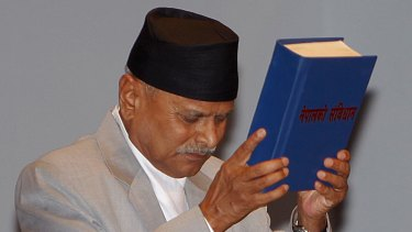 Nepalese President Ram Baran Yadav displays the constitution, formally adopted following a decade of political infighting, in Kathmandu on Sunday.