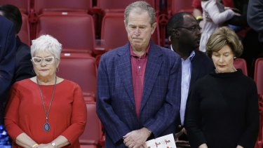 Former president George W Bush observes a moment of silence with his wife, Laura Bush (right), and others in support of the victims of the Paris terrorist attacks, before a college basketball game.