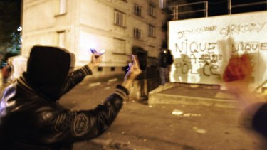"Youths gesture next to a wall with graffiti  that reads ""F--- the police, Sarkozy resign"", in the Renault housing complex of Les Mureaux, north-west of Paris, during the riots of 2005."
