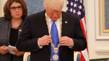 US President Donald Trump looks at the Collar of Abdulaziz Medal after receiving it.