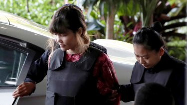 Vietnamese Doan Thi Huong, left, is escorted by police as she arrives for the court hearing.