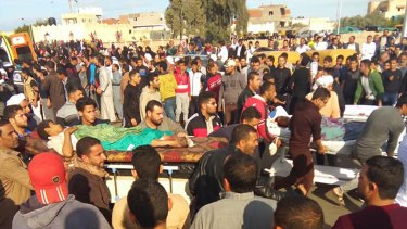 Injured people are evacuated from the scene of a militant attack on a mosque in Bir al-Abd in the northern Sinai Peninsula of Egypt on Friday