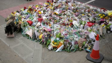 A woman looks at a floral tribute near London Bridge, where eight people died and dozens were seriously injured.
