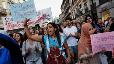 Protesters shout slogans as they hold placards welcoming refugees during a show of solidarity and support for refugees in Madrid, Spain.
