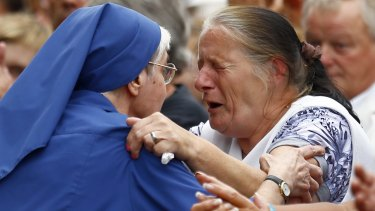 French nun grieves with a woman during a gathering in a town park for a solemn homage to slain priest Father Jacques Hamel in Saint-Etienne-du-Rouvray, Normandy