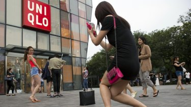 A woman poses for a photo outside the Uniqlo store in Beijing where a steamy video was filmed.