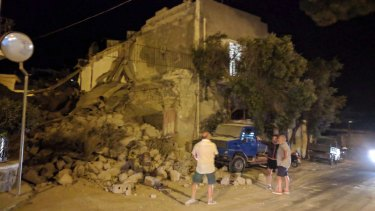People standing near a collapsed building following an earthquake in Casamicciola on the Italian resort island of Ischia.