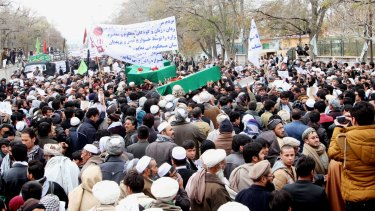 Afghan men carry seven coffins of the slain Hazara in Ghazni province on Tuesday.