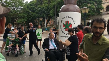 One Nation MP Steve Dickson, Independent MP Rob Pyne and councillor Jonathan Sri lead a rally supporting medicinal cannabis outside Queensland Parliament.