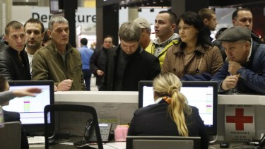 People gather at the airline information desk at Pulkovo Airport in St.Petersburg.