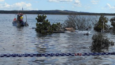 Divers inspect the collapsed area of beach at Inskip Point north of the Sunshine Coast.