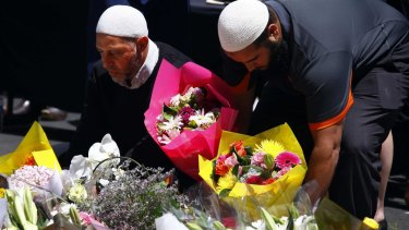 The Muslim community is not a security threat, nor should we be treated or suspected as such: two Australian Muslim men place flowers near the scene of the Lindt cafe siege.