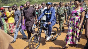 President Pierre Nkurunziza rides a bicycle to cast his vote in the presidential election.