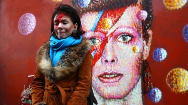 David Bowie fan Rosie Lowery placed flowers at his mural in Brixton, London, after the singer's death was announced on Monday.