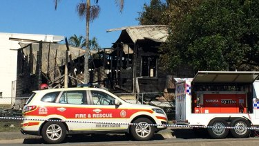 Emergency crews outside the burnt remains of the house.