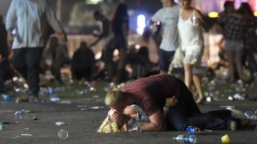 People lie on the ground at a country music festival in Las Vegas after a shots were fired at the concert.