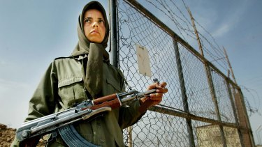 A female fighter of the MEK stands guard at a gate outside their main base at Camp Ashraf, Iraq, 100 kilometres north of Baghdad, in 2003. Residents were transferred to Camp Liberty in 2012.