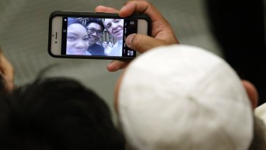 Pope Francis poses for a selfie with a couple attending his weekly general audience last month